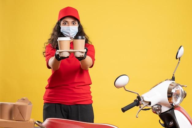 Corriere femminile vista frontale in uniforme rossa con tazze di caffè su sfondo giallo consegna del lavoratore covid- virus dell'uniforme del lavoro pandemico
