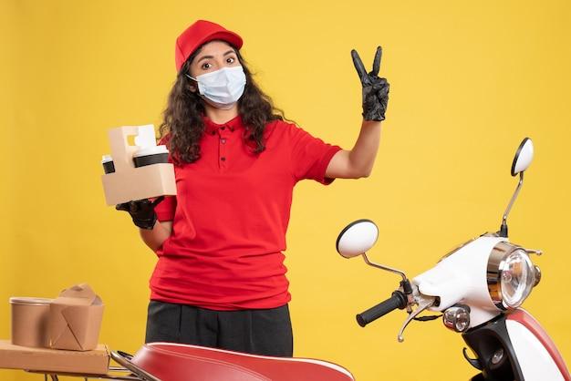 Corriere femminile vista frontale in uniforme rossa con tazze di caffè su sfondo giallo consegna del lavoratore covid- virus del servizio uniforme pandemico