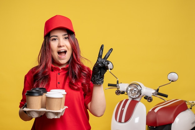 Front view of female courier in red uniform with coffee on a yellow wall