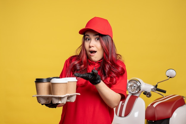 Front view of female courier in red uniform with coffee on the yellow wall