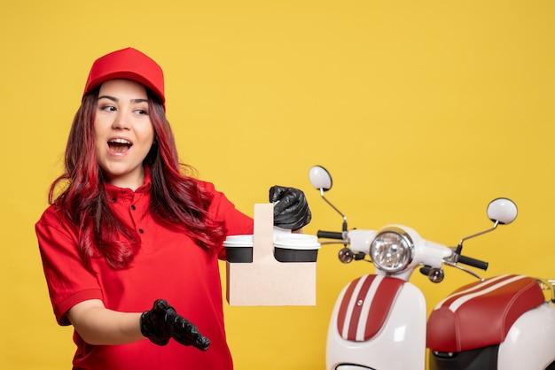 Vista frontale del corriere femminile in uniforme rossa con caffè sulla parete gialla