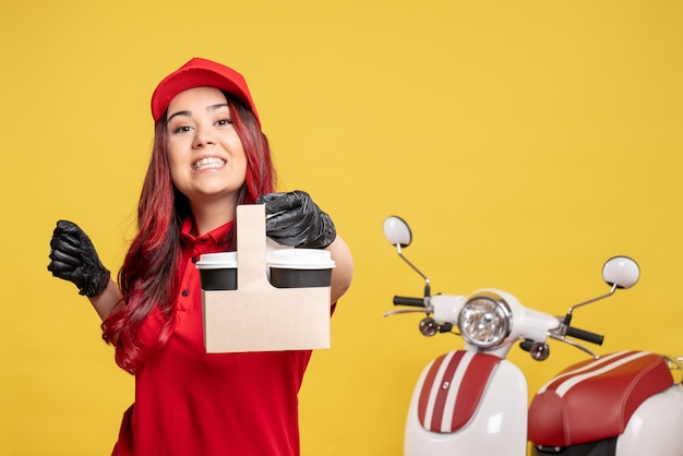 Front view of female courier in red uniform with coffee on yellow wall