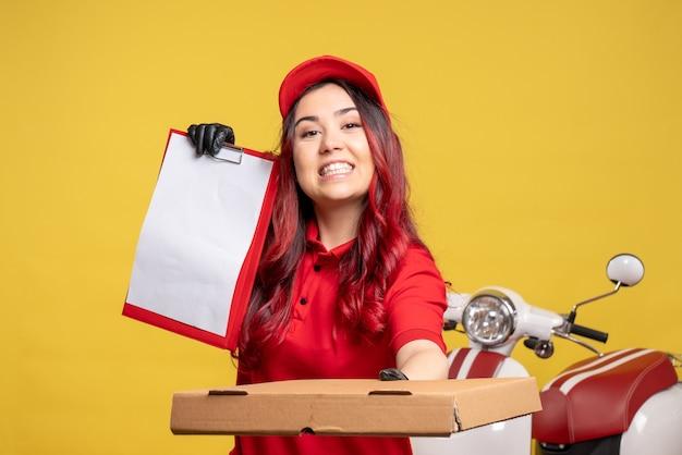 Vista frontale del corriere femminile in uniforme rossa con nota di file e scatola di cibo sulla parete gialla