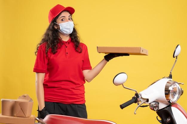 Corriere femminile vista frontale in uniforme rossa con scatola della pizza sullo sfondo giallo lavoratore di servizio covid- virus pandemico consegna del lavoro