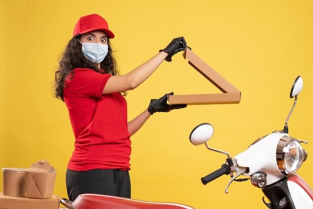 Corriere femminile vista frontale in uniforme rossa con scatola della pizza su sfondo giallo lavoro di consegna del lavoratore covid- servizio pandemico virus