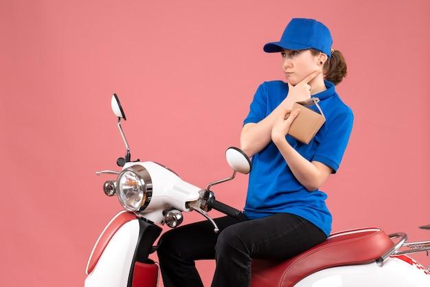 Corriere femminile di vista frontale che si siede sulla bici con le tazze di caffè sul cibo dell'operaio di lavoro di consegna di servizio uniforme di colore rosa