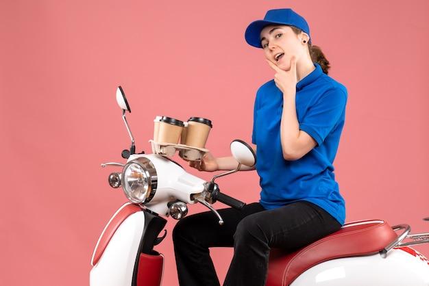 Corriere femminile vista frontale che si siede sulla bici con le tazze di caffè sul cibo dell'operaio di consegna uniforme di colore di lavoro rosa