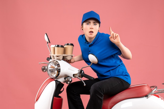 Front view female courier sitting on bike with coffee cups on pink job color uniform worker food service delivery