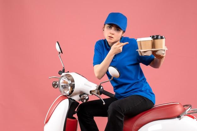 Вид спереди женщина-курьер, сидящая на велосипеде с кофейными чашками на розовой униформе, работник общественного питания