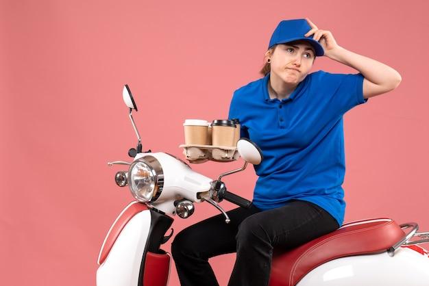 Вид спереди женщина-курьер, сидящая на велосипеде с кофейными чашками на розовой работе, униформа, доставка, работник общественного питания