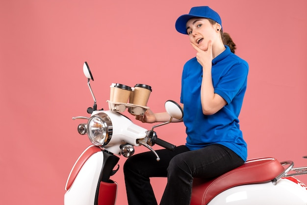 Вид спереди женщина-курьер, сидящая на велосипеде с кофейными чашками на розовой работе, униформа доставщика еды