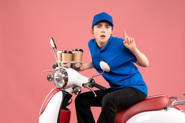 ピンクの仕事の色の均一な労働者のフードサービスの配達でコーヒーカップと自転車に座っている正面図の女性の宅配便