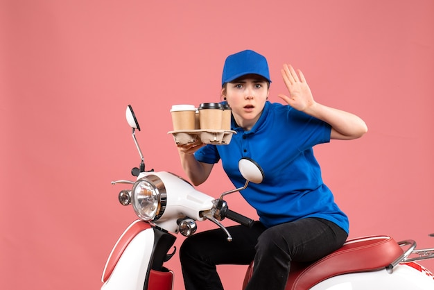 ピンクの仕事の色の制服労働者サービスの提供にコーヒーカップと自転車に座っている正面図の女性の宅配便