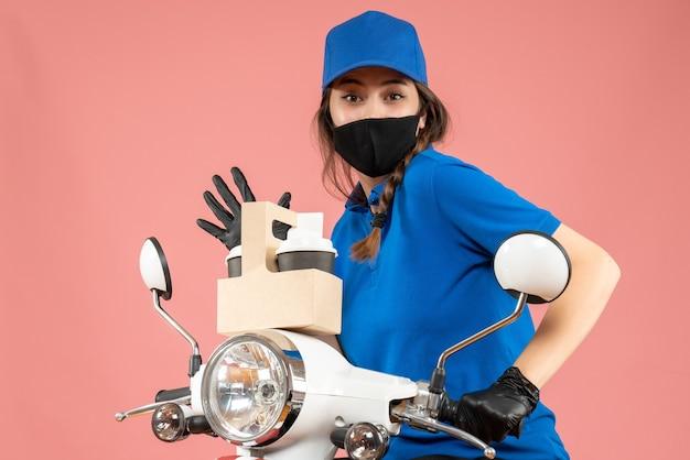Vista frontale del corriere femminile che indossa maschera medica nera e guanti che tengono ordini su sfondo pesca