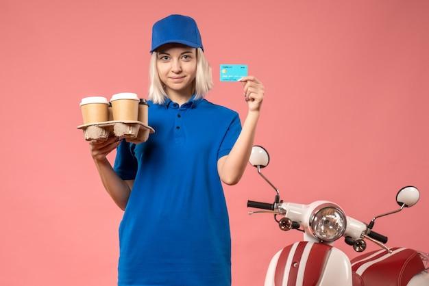 Corriere femminile di vista frontale con carta di credito e caffè di consegna sul colore del lavoro uniforme di consegna servizio di lavoro rosa