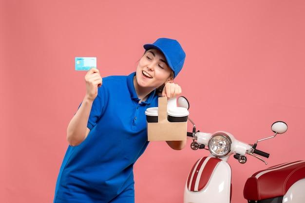 Вид спереди женщина-курьер с кофе и банковской картой на розовой рабочей униформе службы доставки на велосипеде с женщиной-пиццей