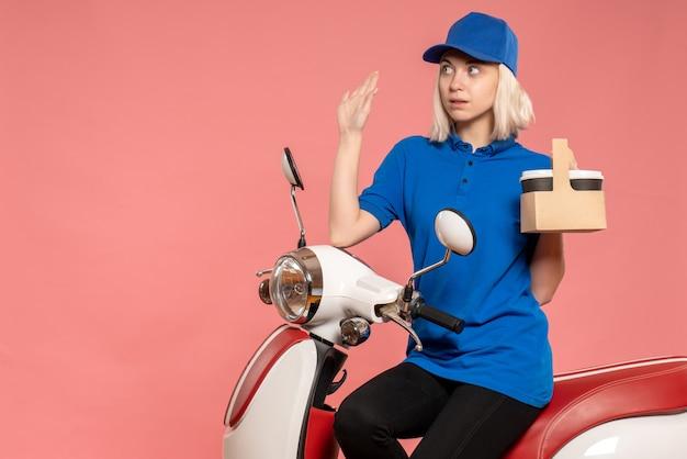 ピンクの配達サービスの仕事の色の労働者の制服の仕事でコーヒーカップと正面図の女性の宅配便