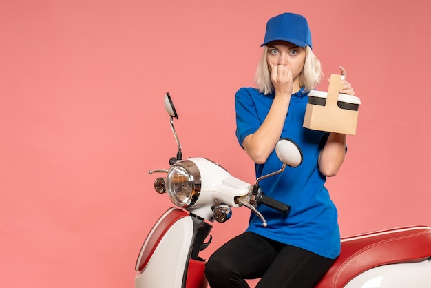 Front view female courier with coffee cups on pink delivery service color worker uniform job