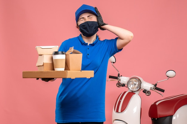 ピンクのパンデミック労働者が共同で均一な仕事サービスを提供するコーヒーと食べ物を配達する正面図の女性宅配便