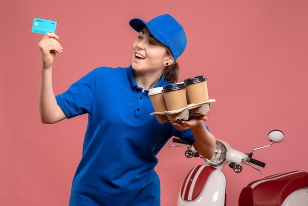 Corriere femminile di vista frontale con caffè di consegna e carta di credito sul lavoratore di servizio uniforme di lavoro di consegna lavoro bici rosa