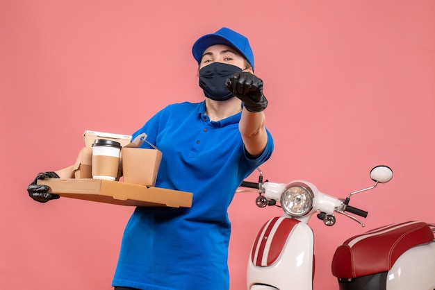 Front view female courier with delivery coffee and food on a pink pandemic work delivery worker covid- uniform job service