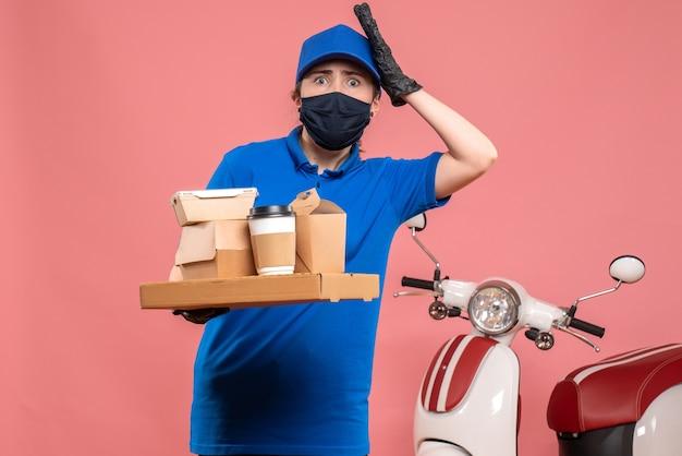 Corriere femminile di vista frontale con caffè di consegna e cibo sul servizio covid-uniforme dell'operaio di consegna del lavoro pandemico rosa
