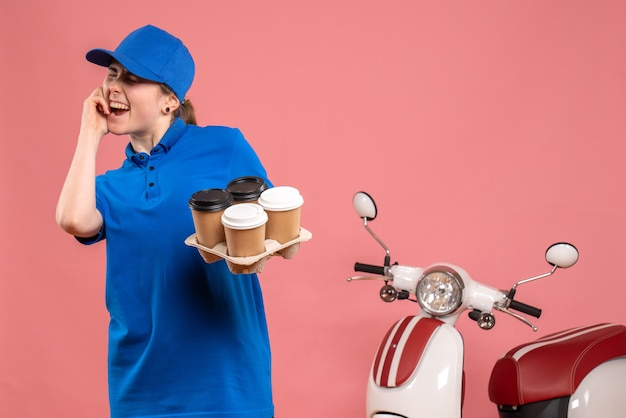 Corriere femminile di vista frontale con caffè di consegna sulla bici dell'operaio di servizio uniforme di lavoro di consegna del lavoro del pavimento rosa Foto Gratuite