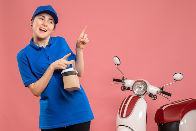 Corriere femminile di vista frontale con caffè di consegna sull'uniforme rosa della bici della donna del lavoratore di servizio di consegna del lavoro