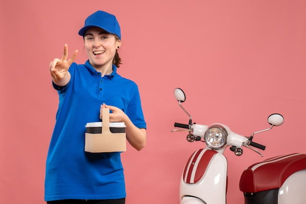Corriere femminile di vista frontale con caffè di consegna sull'uniforme rosa della bici della donna del lavoratore di servizio di consegna del lavoro Foto Gratuite