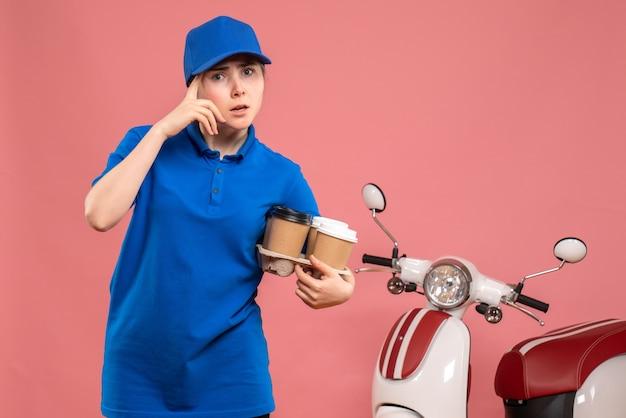 Corriere femminile di vista frontale con caffè di consegna sul lavoro rosa della bici del lavoratore di servizio dell'uniforme di consegna del lavoro