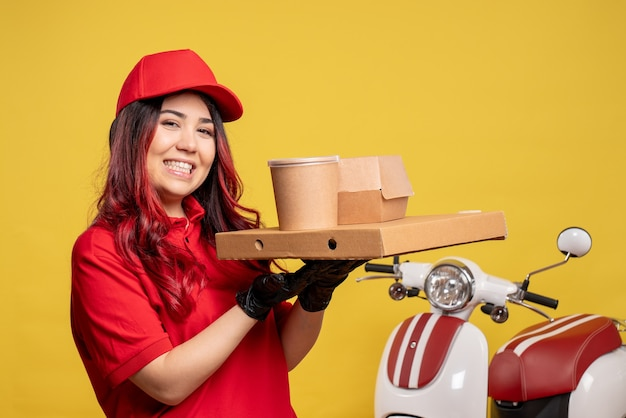 Front view of female courier with delivery food and dessert on yellow wall