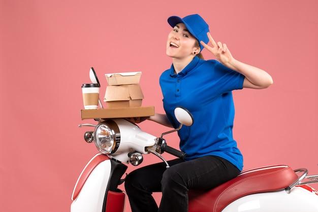 Вид спереди женщина-курьер с пакетами еды и коробками на розовом рабочем месте. цветной рабочий, доставка еды, велосипедная униформа.