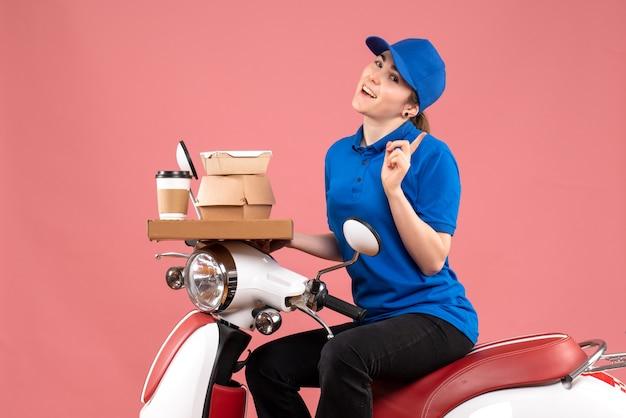 Вид спереди женский курьер с пакетами еды и коробками на розовой работе, цветная служба доставки еды