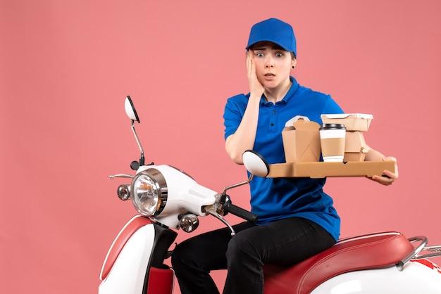 Вид спереди женский курьер с пакетами еды и коробками на розовых рабочих тонах. служба доставки еды на велосипеде.