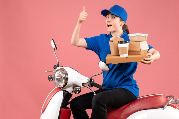 Front view female courier with food packages and boxes on pink job color worker food delivery bike service