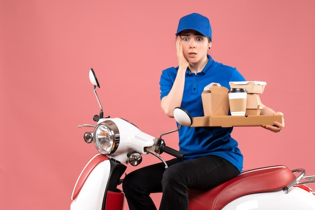 Corriere femmina vista frontale con pacchi di cibo e scatole su colore rosa lavoro lavoratore servizio uniforme bici consegna cibo