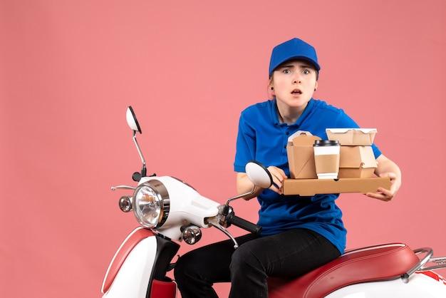 Corriere femminile di vista frontale con i pacchetti di cibo e le scatole sul servizio uniforme della bici di consegna del cibo dell'operaio di lavoro rosa