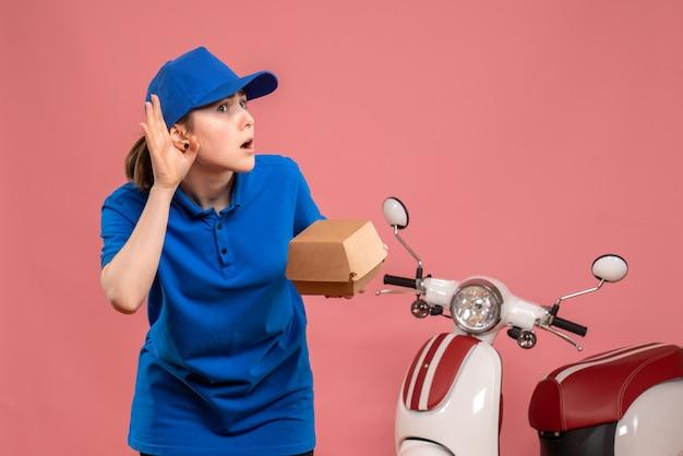Corriere femminile di vista frontale con poco pacchetto dell'alimento che ascolta sulla donna della pizza dell'operaio della bici di lavoro di servizio dell'uniforme di consegna del lavoro rosa