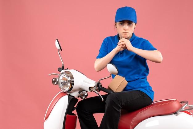 Курьер-женщина, вид спереди с маленьким пакетом продуктов на розовом велосипеде для доставки еды рабочего цвета