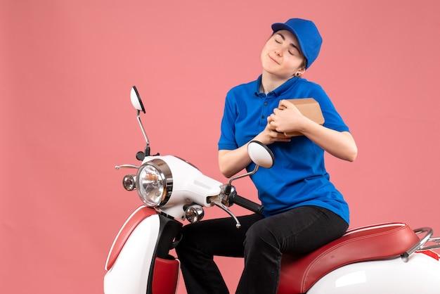 ピンクのジョブカラーの制服労働者の食品配達自転車に小さな食品パッケージを持つ正面図の女性の宅配便