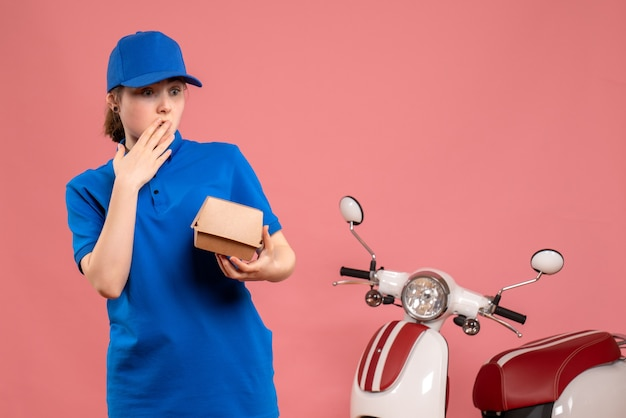 Corriere femminile vista frontale con poco pacchetto di cibo sorpreso sul lavoro di bici servizio uniforme consegna lavoro rosa
