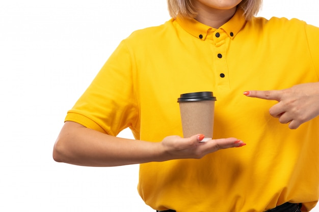 A front view female courier in yellow shirt holding coffee cup on white