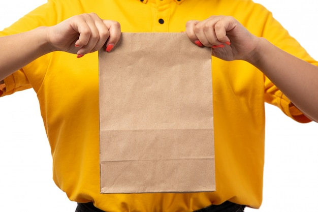A front view female courier in yellow shirt holding food package on white