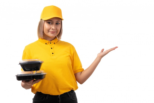 A front view female courier in yellow shirt yellow cap and black jeans holding bowls with food and smartphone smiling on white