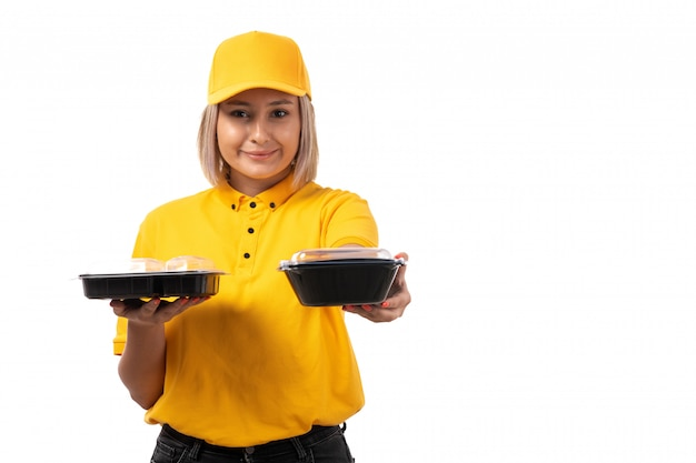 A front view female courier in yellow shirt yellow cap and black jeans holding bowls with food smiling on white