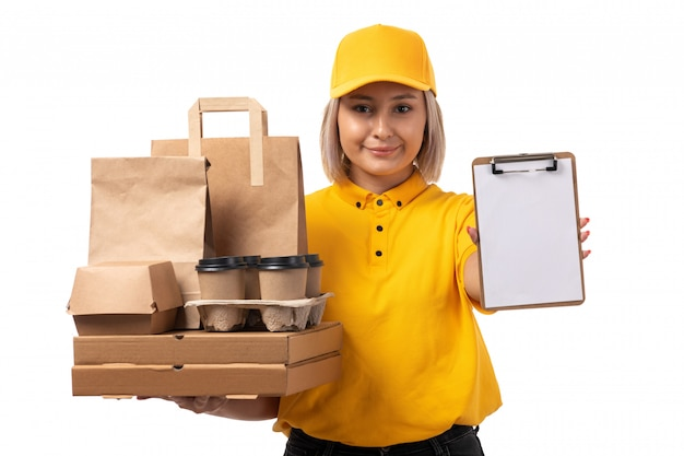 A front view female courier in yellow shirt yellow cap black jeans holding packages and boxes smiling on white