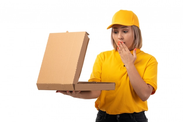 A front view female courier in yellow shirt yellow cap black jeans holding pizza box shocked on white