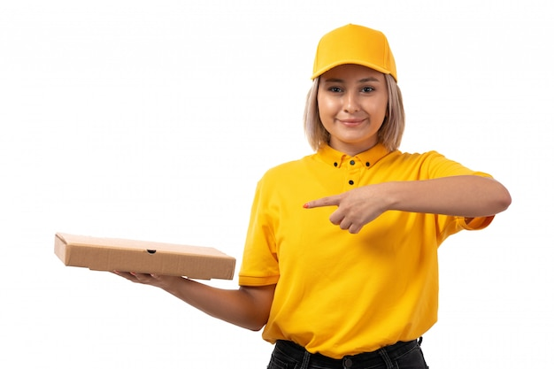 A front view female courier in yellow shirt yellow cap and black jeans holding pizza box smiling on white