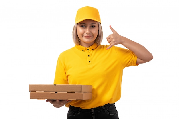A front view female courier in yellow shirt yellow cap and black jeans holding pizza boxes showing phone call sign smiling on white