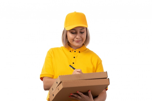 A front view female courier in yellow shirt yellow cap black jeans holding pizza boxes writing smiling on white